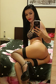 Black haired escort on a bed taking a selfie in a mirror