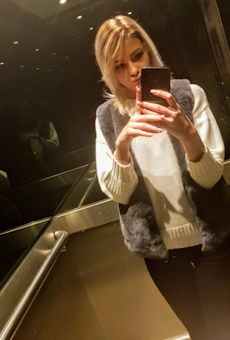 Teen taking a selfie in a lift with mirrors