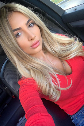 Sexy escort in a red top taking a selfie in a sports car