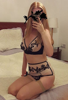 Submissive girl sitting on a bed taking a selfie